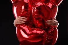 Las manos abrazan un manojo de primer de los globos en un fondo negro Foto de archivo libre de regalías