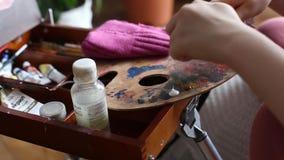 Las manos abren el tubo de la pintura y de la pintura del apretón sobre la paleta Paleta del artista con la pintura y los cepillo almacen de video