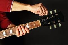 Las manos adaptan la guitarra eléctrica en fondo oscuro Foto de archivo libre de regalías