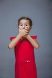 Las manos adolescentes del niño de la muchacha que cubren su boca sienten Imagenes de archivo