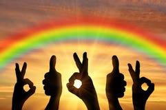 Las manos alcanzan para el cielo en la puesta del sol y el arco iris Foto de archivo