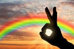 Las manos alcanzan para el cielo en la puesta del sol y el arco iris Fotografía de archivo libre de regalías