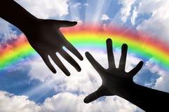 Las manos alcanzan para el cielo en la puesta del sol y el arco iris Foto de archivo libre de regalías