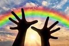 Las manos alcanzan para el cielo en la puesta del sol y el arco iris Imágenes de archivo libres de regalías