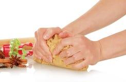 Las manos amasan la pasta para las galletas de la Navidad foto de archivo libre de regalías