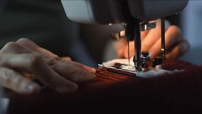 Las manos ascendentes cercanas cosen la tela a cuadros Aguja de la m?quina de coser que hace la costura decorativa con el carril  almacen de video