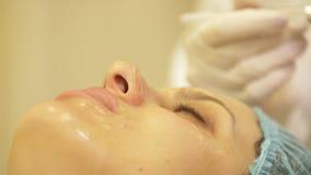 Las manos ascendentes cercanas del cosmetólogo aplican la crema en cara paciente después del tratamiento y del masaje metrajes