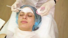 Las manos ascendentes cercanas del cosmetólogo aplican la crema en cara paciente después del tratamiento y del masaje almacen de video