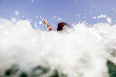 Las manos atractivas de las ondas del mar de la nadada de la muchacha para arriba salpican detrás la visión Fotografía de archivo libre de regalías
