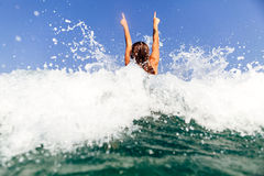 Las manos atractivas de las ondas del mar de la nadada de la muchacha para arriba salpican detrás la visión Fotografía de archivo