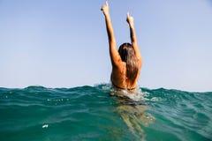 Las manos atractivas de las ondas del mar de la nadada de la muchacha para arriba salpican detrás la visión Imagenes de archivo