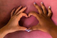 Las manos blancas y negras de novias forman un corazón de fingeres contra racismo fotografía de archivo