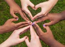 Las manos blancos y negros en corazón forman, concepto interracial de la amistad imagen de archivo libre de regalías