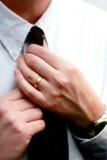 Las manos casadas enderezan una corbata Imagenes de archivo