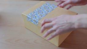 Las manos cierran una actual caja Concepto de los días de fiesta Colores beige y azules