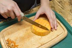 Las manos cocinan con un cuchillo y una calabaza Imágenes de archivo libres de regalías