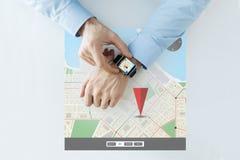 Las manos con el navegador de los gps trazan en el reloj elegante Foto de archivo libre de regalías