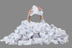 Las manos con el papel machacado vacío alcanzan hacia fuera del montón grande de papeles arrugados Foto de archivo