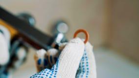 Las manos con guantes del primer de un fontanero instalan una junta en el grifo almacen de metraje de vídeo