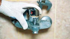 Las manos con guantes del primer del fontanero desinstalan el grifo almacen de metraje de vídeo