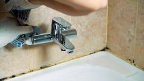 Las manos con guantes del primer del fontanero instalan el grifo en el cuarto de baño almacen de metraje de vídeo