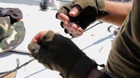 Las manos con guantes del ` s de los hombres desenredan la línea desenrede el enredo de la línea en el fondo del barco almacen de video