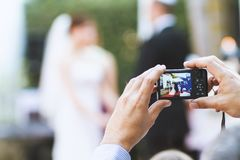Las manos con la cámara digital toman una foto fotos de archivo libres de regalías