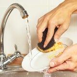 Las manos con la esponja lavan los platos sucios debajo de la agua corriente en cocina Imagen de archivo