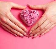 Las manos con la manicura plegable en la dimensión de una variable del corazón Imágenes de archivo libres de regalías