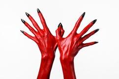 Las manos con los clavos negros, manos rojas de Satanás, tema del diablo rojo de Halloween, en un fondo blanco, aislado Fotos de archivo