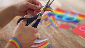 Las manos con las tijeras cortaron la cinta de la conciencia del orgullo gay almacen de video