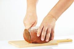 Las manos cortaron el pan de centeno en una tabla de cortar Imagen de archivo