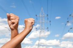 Las manos cruzaron los puños de las demostraciones y las líneas de transmisión de poder contra b Imagen de archivo libre de regalías