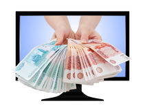 Las manos dan el efectivo ruso fuera de la pantalla de ordenador Imágenes de archivo libres de regalías