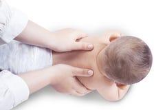 Las manos dan masajes a la espina dorsal del bebé Fotografía de archivo