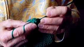Las manos de las abuelas hacen a ganchillo el hilado verde Clip del primer del funcionamiento mayor de la mujer almacen de metraje de vídeo