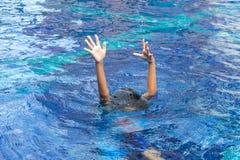 Las manos de ahogan al niño en el agua profunda, necesidad de la ayuda fotografía de archivo