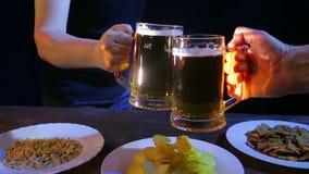 Las manos de amigos en la barra golpearon las tazas de cerveza juntas en un fondo negro almacen de metraje de vídeo