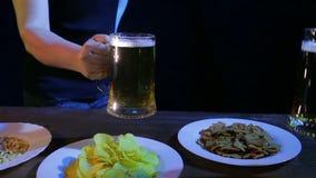Las manos de amigos en la barra golpearon las tazas de cerveza juntas en un fondo negro almacen de video