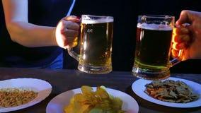 Las manos de amigos en la barra golpearon las tazas de cerveza juntas en un fondo negro metrajes