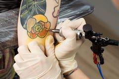 Las manos de amo que dibujan tatto por la máquina Fotografía de archivo