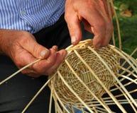 Las manos de anciano que trabajan el bastón para crear una cesta de mimbre Fotografía de archivo libre de regalías