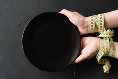 Las manos de ayuno de los weightloss de la dieta rígida vacian la placa foto de archivo libre de regalías