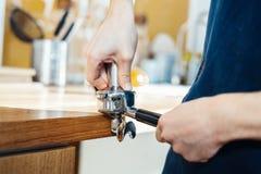 Las manos de Barista que sostienen el portafilter y el café tratan de forzar haciendo un café del café express foto de archivo