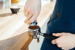 Las manos de Barista que sostienen el portafilter y el café tratan de forzar haciendo un café del café express fotografía de archivo libre de regalías