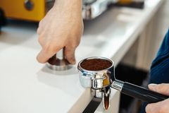 Las manos de Barista que sostienen el portafilter y el café tratan de forzar haciendo un café del café express imagenes de archivo