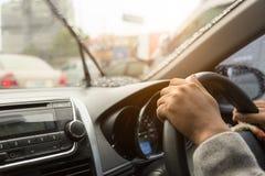 Las manos de conducir al hombre mientras que las manos en la rueda en el coche mientras que está lloviendo pesadamente en el cami imagen de archivo libre de regalías