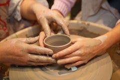 Las manos de dos personas crean el crisol en la rueda de alfarero Foto de archivo libre de regalías