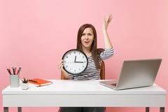 Las manos de extensión irritadas jovenes de la mujer que sostienen el despertador se sientan, trabajo en la oficina con el ordena fotografía de archivo