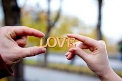 Las manos de hombres y de mujeres con palabra aman Imagen de archivo